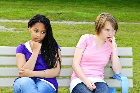 chicas adolescentes: Dos adolescentes aburridos sentados en el banco