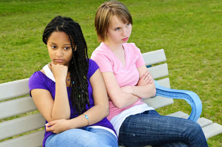 argument: Two bored teenage girls sitting on bench Stock Photo