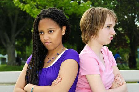 adolescentes chicas: Dos infelices adolescentes sentados en el banco Foto de archivo