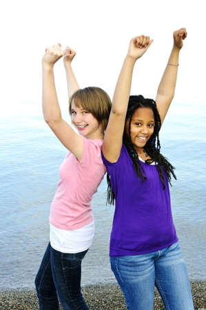Portrait of two teenage girl friends raising arms Stock Photo