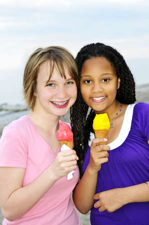 girl licking: Portrait of two teenage girls eating ice cream cones Stock Photo