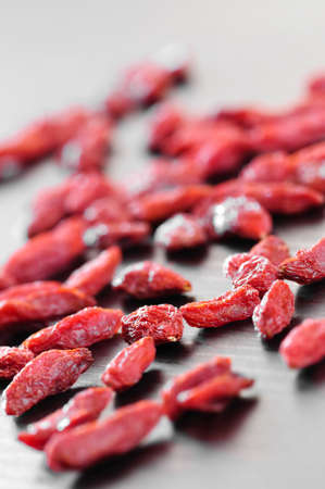 Scattered red dried goji berries on a table photo
