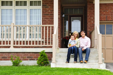 Young family sitting on front steps of house photo