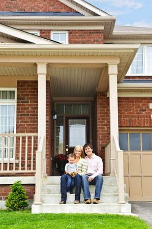 front porch: La familia joven sentado en los escalones frente a la casa Foto de archivo