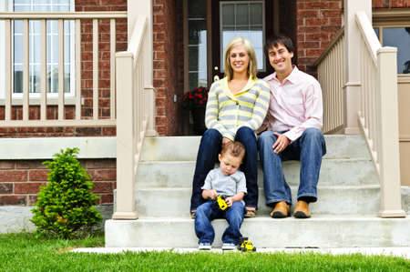 family house: Young family sitting on front steps of house