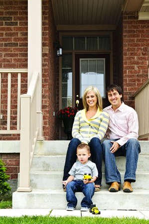 Young family sitting on front steps of house Stock Photo - 5365626