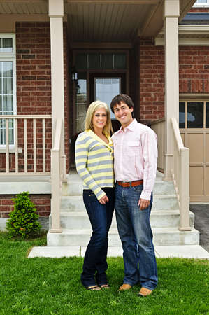 front house: Young happy couple standing in front of house Stock Photo