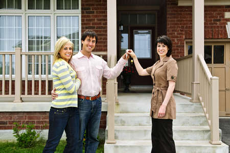 handing: Happy couple getting keys to new house from real estate agent