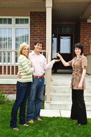 Happy couple getting keys to new house from real estate agent Stock Photo - 5365616