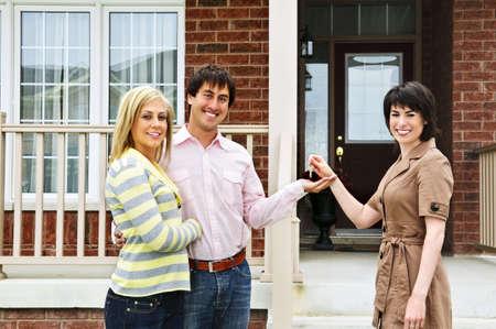 Happy paar krijgt sleutels nieuwe huis van de makelaar in onroerend goed Stockfoto