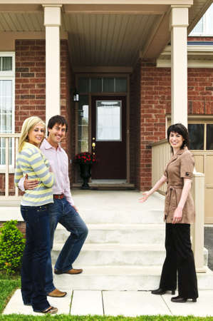Real estate agent with couple welcoming to new home Stock Photo - 5365615