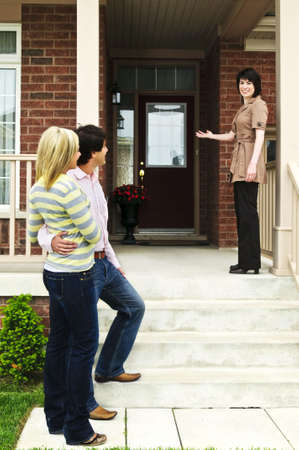 Real estate agent with couple welcoming to new home Imagens