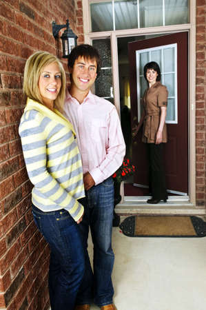 Real estate agent with couple welcoming to new home photo