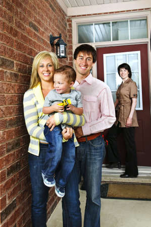Real estate agent with family welcoming to new home photo