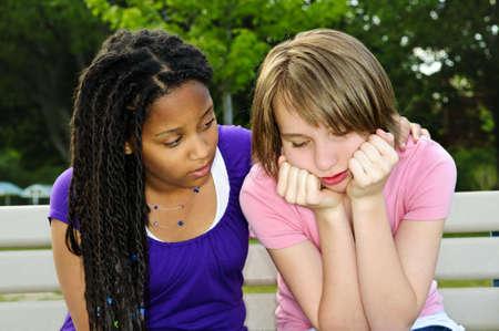 Teenage girl consoling her sad upset friend Reklamní fotografie