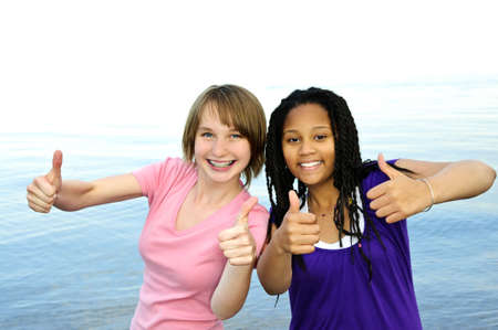 Portrait of two teenage girl friends showing thumbs up photo