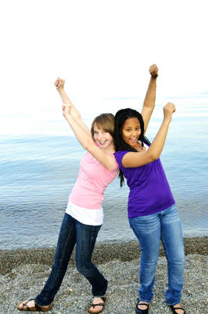 Portrait of two teenage girl friends raising arms photo