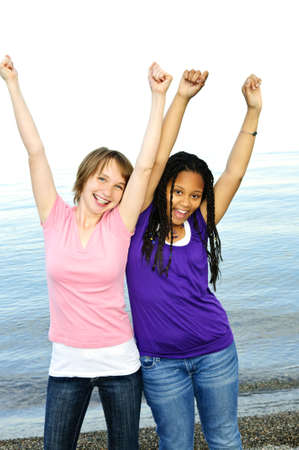 winning woman: Portrait of two teenage girl friends raising arms Stock Photo