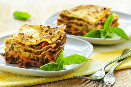 Two servings of fresh baked lasagna on plates photo