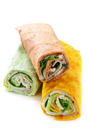 deli sandwich: Three isolated multicolored tortilla wraps with meat and vegetables