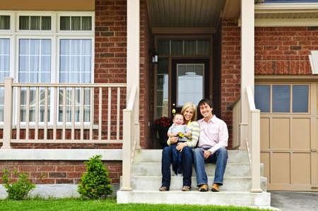 Jeune famille assise sur les marches de la maison