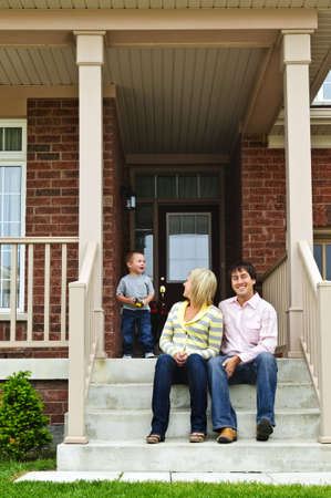 Young family sitting on front steps of house Stock Photo - 5395786