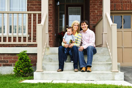 property owners: Young family sitting on front steps of house