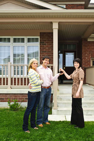 real estate: Happy couple getting keys to new house from real estate agent
