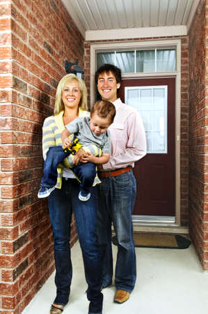 Young happy family in front of house photo