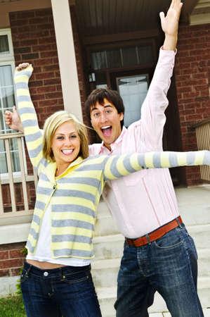 Jong opgewonden paar vieren voor thuis Stockfoto