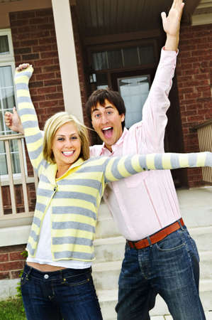 personas festejando: Pareja joven entusiasmados celebrando en frente de una casa