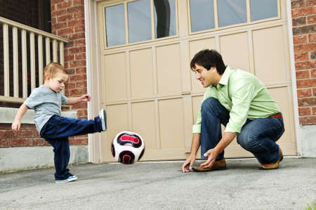 Father teaching son to play soccer on driveway photo