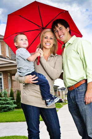 Young happy family under umbrella on sidewalk Banco de Imagens