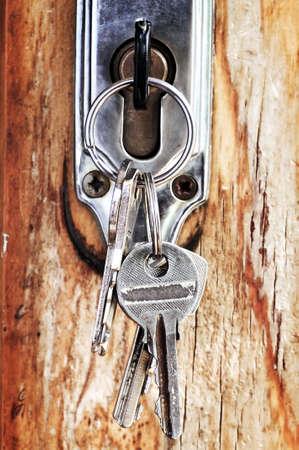 Set of keys in lock of old wooden door photo