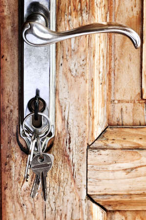 deadbolt: Set of keys in lock of old wooden door Stock Photo