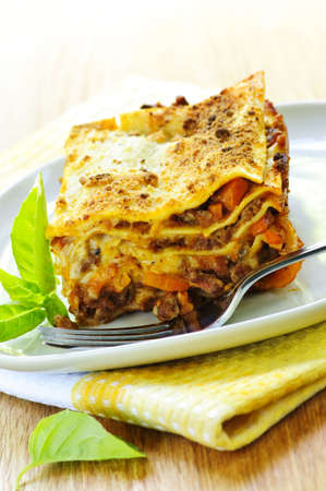 Serving of fresh baked lasagna on a plate photo
