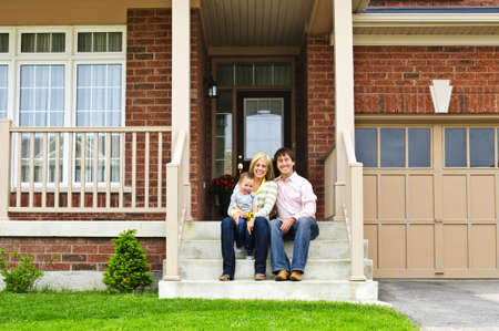 Young family sitting on front steps of house Stock Photo - 5437199