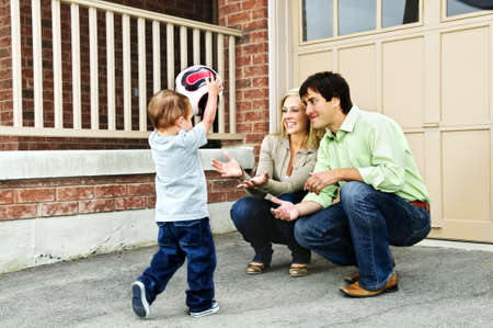 Happy young family playing soccer with toddler on driveway photo