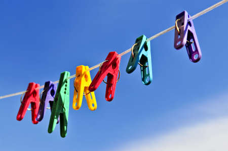 pegs: Colorful clothes pegs on line against blue sky Stock Photo