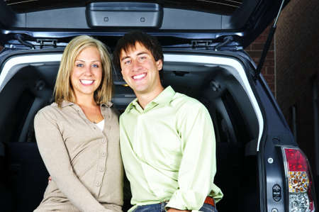 Happy young couple sitting at back of car photo