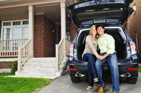 open house: Happy young couple sitting at back of car on driveway