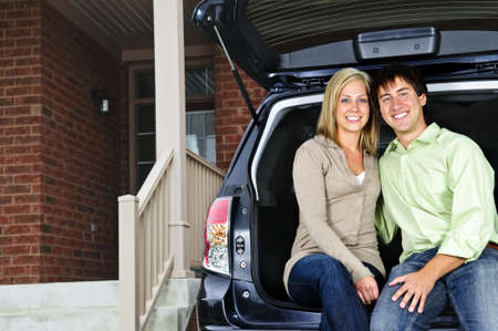 Happy young couple sitting at back of car on driveway photo