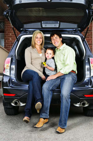 Happy young family sitting at back of car photo