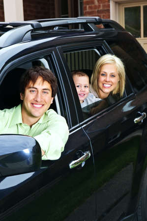 Happy young family sitting in black car looking out windows photo