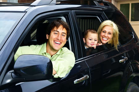 Happy young family sitting in black car looking out windows Stok Fotoğraf
