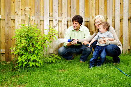 Happy family in backyard watering plant with hose 스톡 콘텐츠