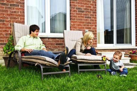 Happy familie ontspannen in de achtertuin van nieuwe thuis met peuter