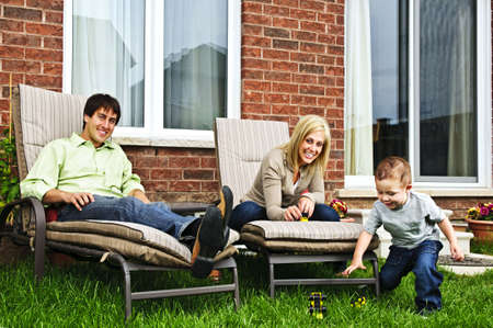 back yard: Happy family relaxing in backyard of new home with toddler Stock Photo