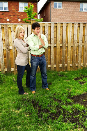seeding: Young couple worried about growing lawn in backyard of new home