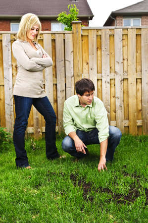 Young couple worried about growing lawn in backyard of new home photo